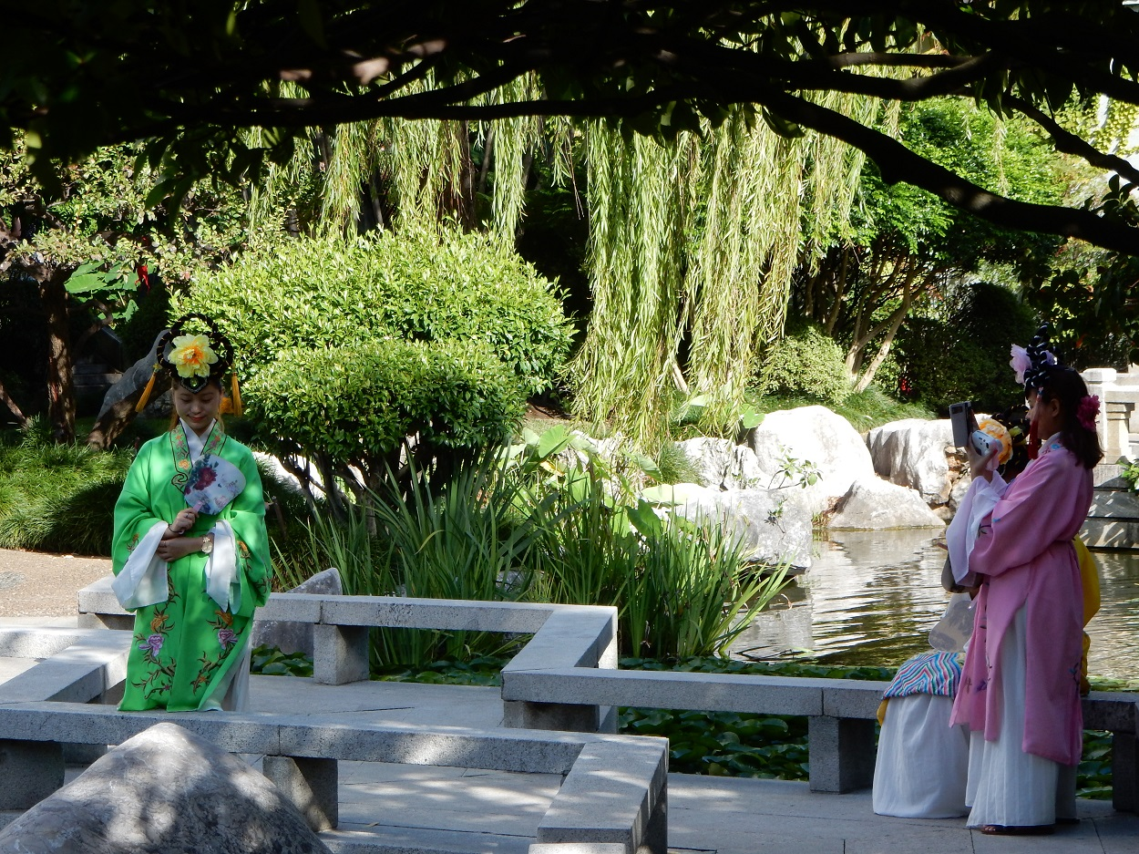 Young Chinese girls in traditional dress taking pictures in the garden